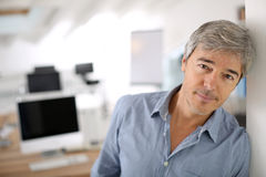 Homme d'affaires mûr au bureau se penchant sur le mur Photos libres de droits