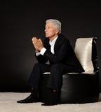 Homme d'affaires mûr de prière s'asseyant dans la chaise Photographie stock libre de droits
