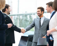 Homme d'affaires mûr se serrant la main pour sceller une affaire avec son associé et collègues dans un bureau moderne Photographie stock