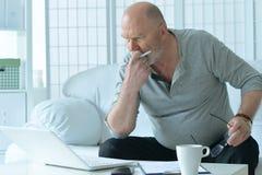 Homme d'affaires mûr travaillant avec l'ordinateur portatif Image libre de droits