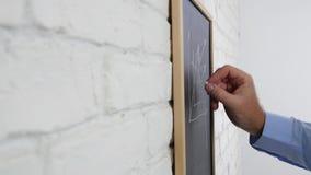 Homme d'affaires Make un plan d'action traçant un diagramme sur un panneau de craie clips vidéos
