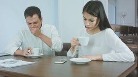 Homme d'affaires malade éternuant tandis qu'associé féminin inquiété vérifiant sa température principale clips vidéos