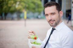 Homme d'affaires mangeant de la salade pour la pause de midi photographie stock