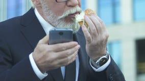 Homme d'affaires mangeant l'hamburger tandis qu'utilisant le téléphone, mauvaise nutrition due au mode de vie occupé clips vidéos