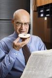 Homme d'affaires mangeant le bagel Photographie stock
