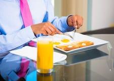 Homme d'affaires mangeant le petit déjeuner Photographie stock libre de droits