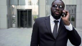 Homme d'affaires marchant à partir du travail, parlant par le téléphone avec des associés, carriériste image stock