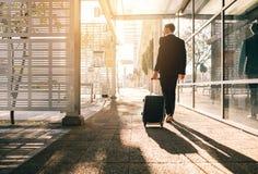 Homme d'affaires marchant avec le sac en dehors de l'aéroport Images stock