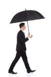 Homme d'affaires marchant avec un parapluie Images libres de droits