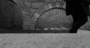 Homme d'affaires marchant dans une allée étroite dans la ville Image stock