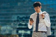 Homme d'affaires marchant dehors utilisant son téléphone intelligent images stock