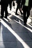 Homme d'affaires marchant rapidement sur le trottoir de ville utilisant le costume noir et la chemise verte, se tenant d'autres h Image stock