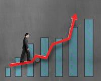Homme d'affaires marchant sur la flèche rouge de croissance avec le diagramme Images libres de droits