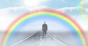 Homme d'affaires marchant sur la route avec l'arc-en-ciel photos stock