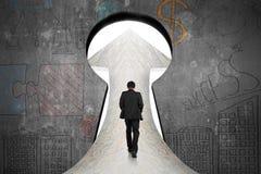 Homme d'affaires marchant sur la route de marbre vers la porte de trou de la serrure avec le dood Photographie stock libre de droits