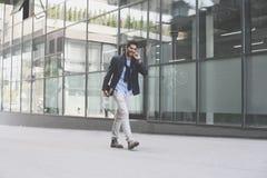 Homme d'affaires marchant sur la rue et tenant iPod L'espace f photos stock