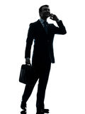 Homme d'affaires marchant sur la silhouette de téléphone Images stock