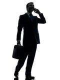Homme d'affaires marchant sur la silhouette de téléphone Photographie stock libre de droits