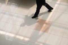 Homme d'affaires marchant sur le plancher carrelé images libres de droits