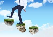 Homme d'affaires marchant vers le haut des étapes des plates-formes de flottement de roche en ciel Image libre de droits