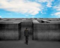 Homme d'affaires marchant vers le labyrinthe 3D concret avec le ciel bleu Photos stock