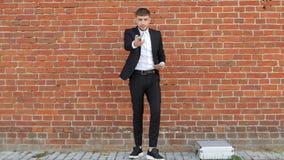 Homme d'affaires masculin de jeune caucasin en euro argent de comptes noirs de costume sur un fond de mur de briques, vol, interm banque de vidéos