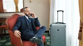 Homme d'affaires masculin de sourire sûr parlant utilisant le smartphone ayant le voyage d'affaires clips vidéos