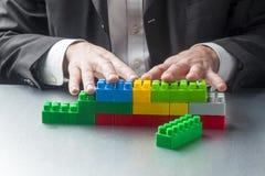 Homme d'affaires masculin jouant avec des briques d'enfants comme métaphore de travail d'équipe Image libre de droits