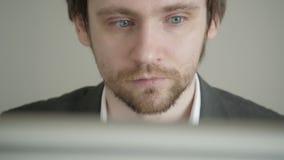 Homme d'affaires masculin Looking à l'écran d'ordinateur dans le bureau Front View banque de vidéos