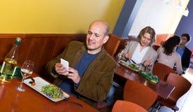 Homme d'affaires masculin supérieur avec la nourriture et le smartphone Images stock