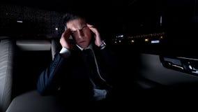 Homme d'affaires massant des temples dans la voiture sur le chemin de la maison, mal de tête fort, le travail stressant photos libres de droits