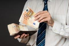 Homme d'affaires mettant des billets de banque dans son portefeuille Pile d'argent de cinquante euros L'homme d'affaires tient l' Images libres de droits
