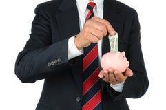 Homme d'affaires mettant l'argent à la tirelire images stock