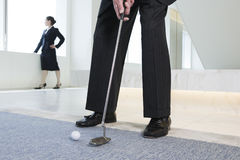 Homme d'affaires mettant la bille de golf. Photo stock