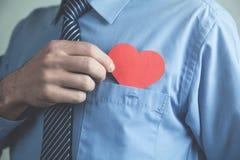 Homme d'affaires mettant le coeur rouge dans une poche de chemise Images libres de droits