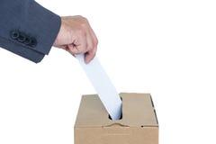 Homme d'affaires mettant le vote dans la boîte de vote Photos stock