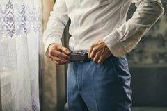 Homme d'affaires mettant sur une ceinture, une mode et un concept d'habillement, groo photographie stock libre de droits