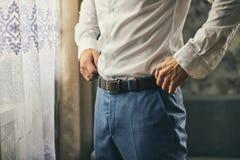 Homme d'affaires mettant sur une ceinture, une mode et un concept d'habillement, groo photo stock