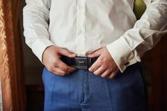 Homme d'affaires mettant sur une ceinture, une mode et un concept d'habillement, marié étant prêt pendant le matin avant cérémoni photographie stock libre de droits