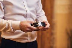 Homme d'affaires mettant sur une ceinture, une mode et un concept d'habillement, marié étant prêt pendant le matin avant cérémoni photographie stock