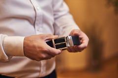 Homme d'affaires mettant sur une ceinture, une mode et un concept d'habillement, marié étant prêt pendant le matin avant cérémoni photo stock