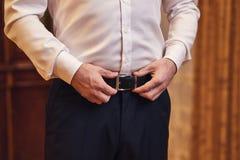 Homme d'affaires mettant sur une ceinture, une mode et un concept d'habillement, marié étant prêt pendant le matin avant cérémoni photo libre de droits