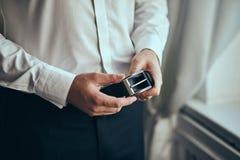 Homme d'affaires mettant sur une ceinture, une mode et un concept d'habillement, marié étant prêt pendant le matin avant cérémoni photos stock