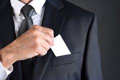 Homme d'affaires mettant une carte de visite professionnelle vierge de visite dans sa poche de poitrine de vestes images stock