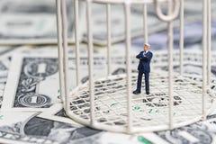 Homme d'affaires miniature à l'intérieur de cage à oiseaux sur la pile du billet de banque du dollar Photo libre de droits