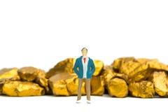 Homme d'affaires miniature de figure ou petites personnes avec la pile des pépites d'or ou du minerai d'or sur le fond blanc, la  photographie stock