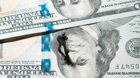 Homme d'affaires miniature de figurine avec 100 dollars de billet de banque sur le fond Photographie stock libre de droits