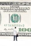 Homme d'affaires miniature se tenant devant le dollar US Images libres de droits