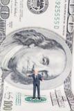 Homme d'affaires miniature se tenant sur le dollar US Image libre de droits