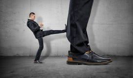 Homme d'affaires minuscule donnant un coup de pied les jambes énormes des autres photographie stock